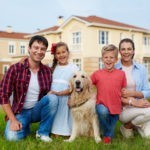 Portrait of successful happy family with two children, boy and girl, and their golden retriever dog sitting together on green grass lawn against background of new expensive houses, smiling and looking at camera